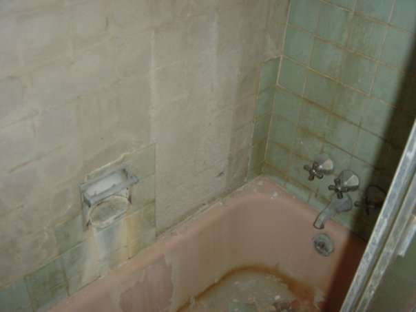 Closeup of the old bathtub and tile that had started to fall off.