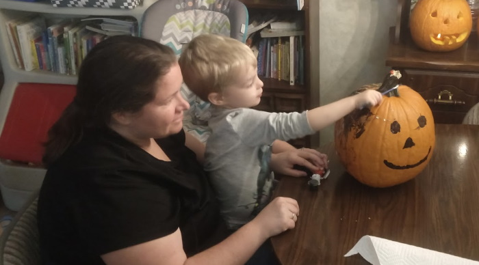 My son and wife painting a pumpkin.
